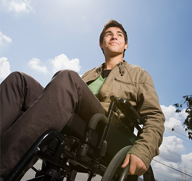 Young man in wheelchair looking up at the sky